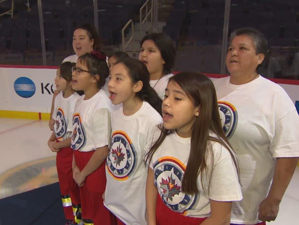 Des enfants et une adulte sur un terrain de hockey qui chantent.