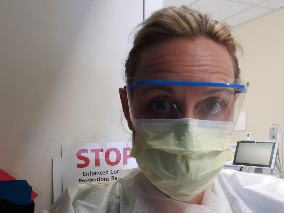 Une infirmière porte de grosses lunettes, un masque et un habit de protection contre le virus.