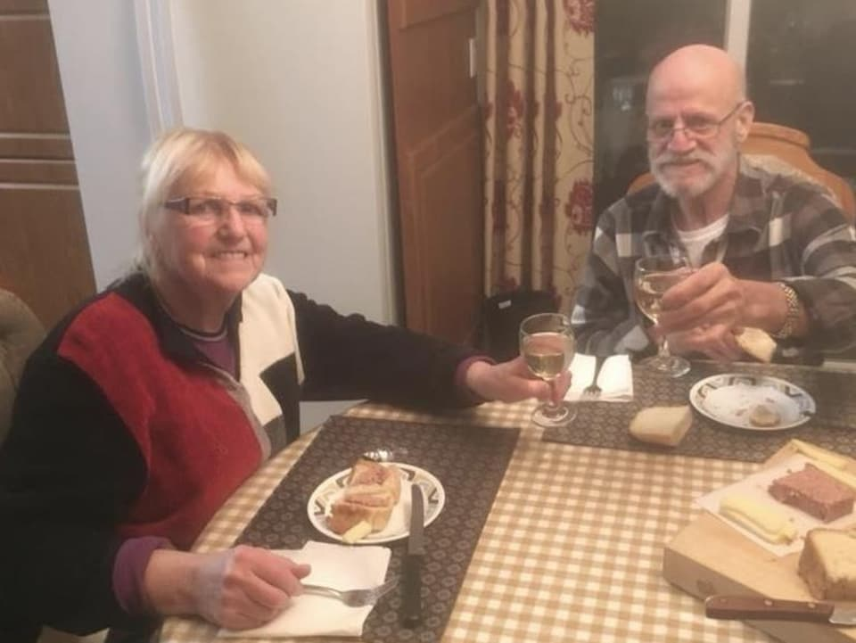 Un homme et une femme trinquent un verre de vin.