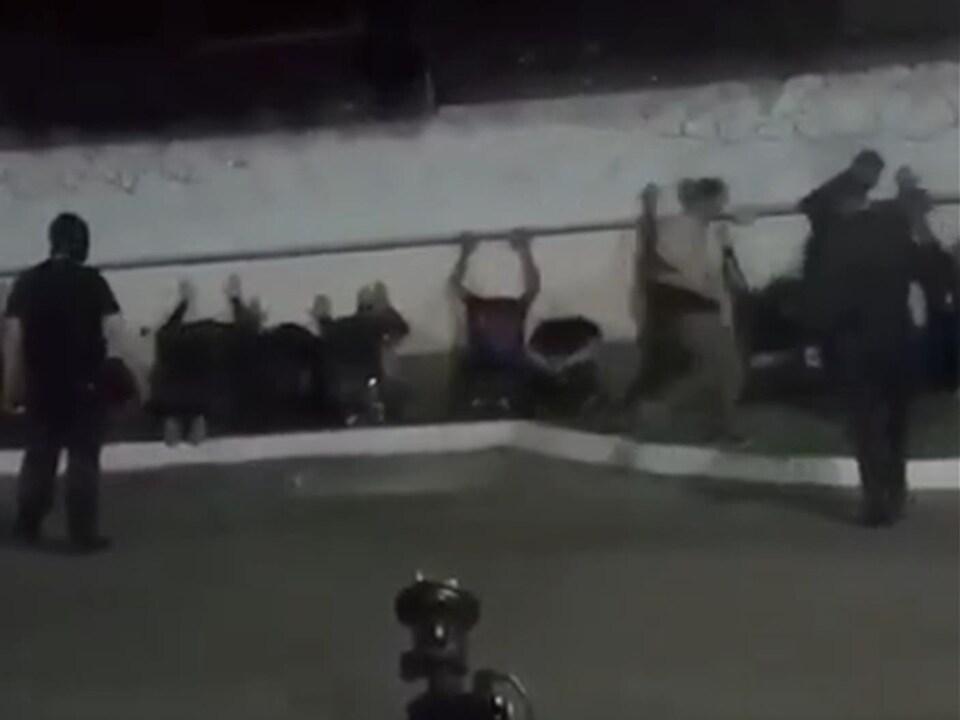 Des hommes alignés le long d'un mur.