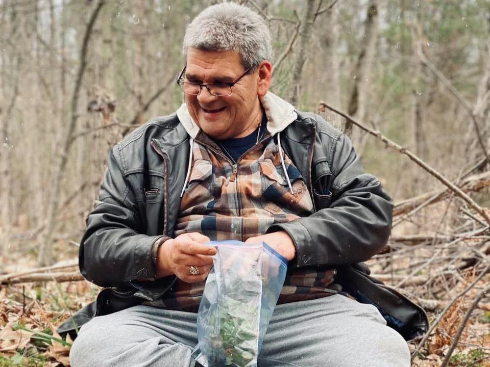 Portrait de l'homme assis sur le sol dans une forêt.