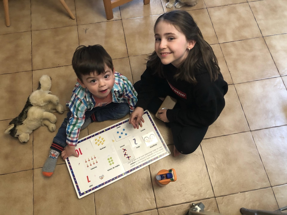 On voit le petit Raphaël et la jeune Eloïse par terre, qui regardent vers le haut la caméra et sourient. Raphaël tient un livre ouvert devant lui. Quelques jouets jonchent le sol.