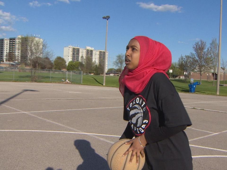 Yasin Said effectue un lancé avec un ballon de basketball.