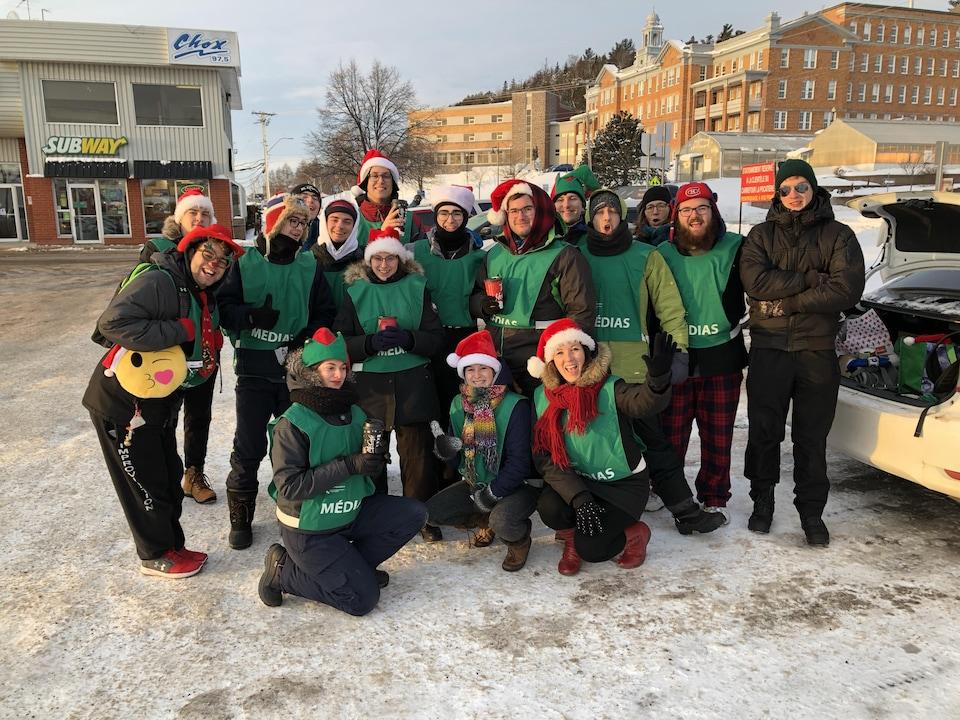 Un groupe de 17 étudiants, habillés d'un dossard de bénévole et de tuques de Noël, sourient à la caméra.