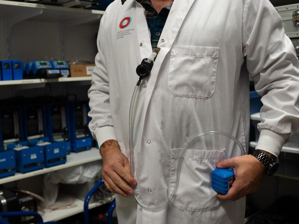 Un homme en sarrau fait la démonstration de l'utilisation d'une petite pompe.