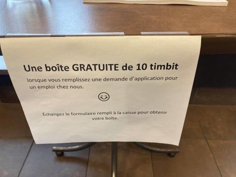 Une feuille sur laquelle il est écrit : Une boîte gratuite de 10 Timbits lorsque vous remplissez une demande d'application pour un emploi chez nous.