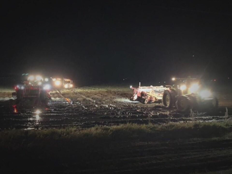 Deux tracteurs, les phares allumés, tirent des récolteuses dans un champ boueux la nuit avec des camions à l'arrière-plan.