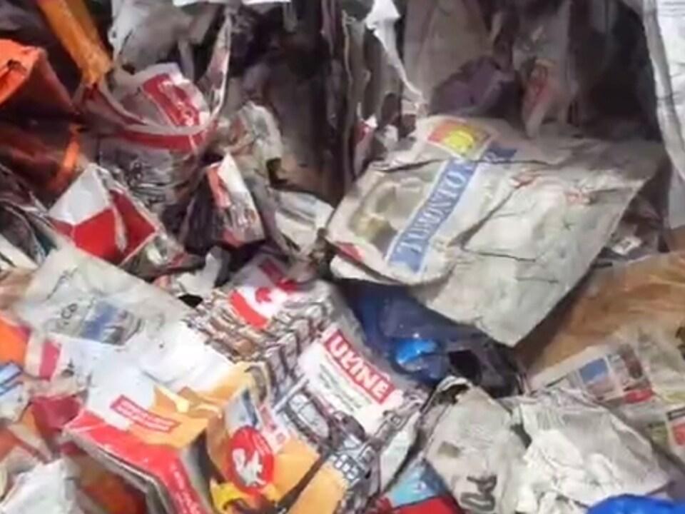 Un exemplaire du journal Toronto Star et un drapeau canadien imprimé sur un autre bout de papier sont parmi les matières recyclées.