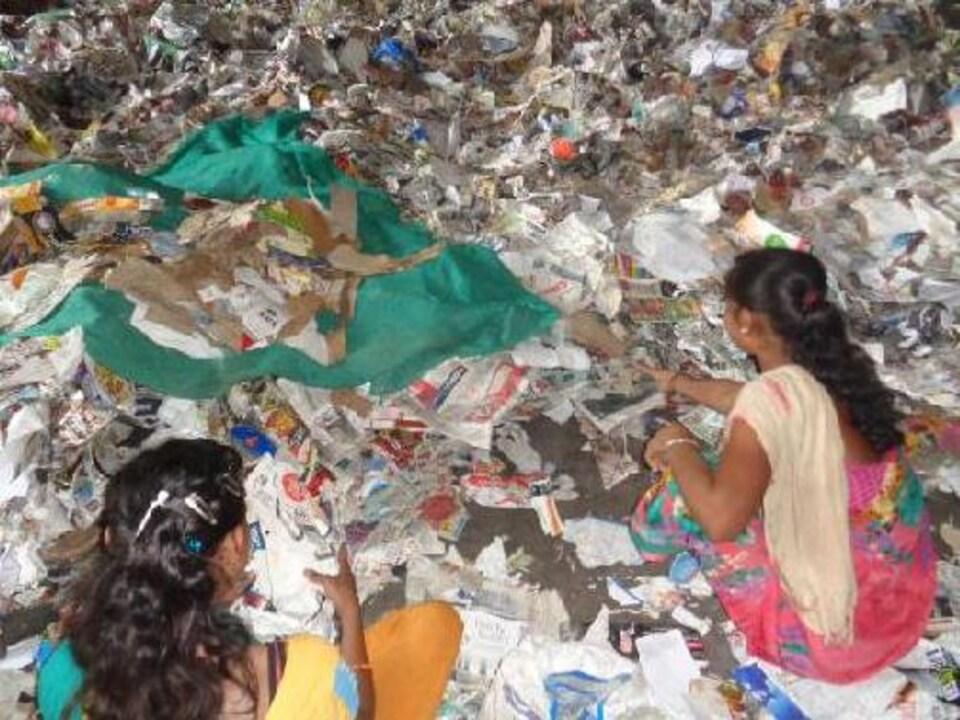Des travailleuses indiennes entourées de papier.