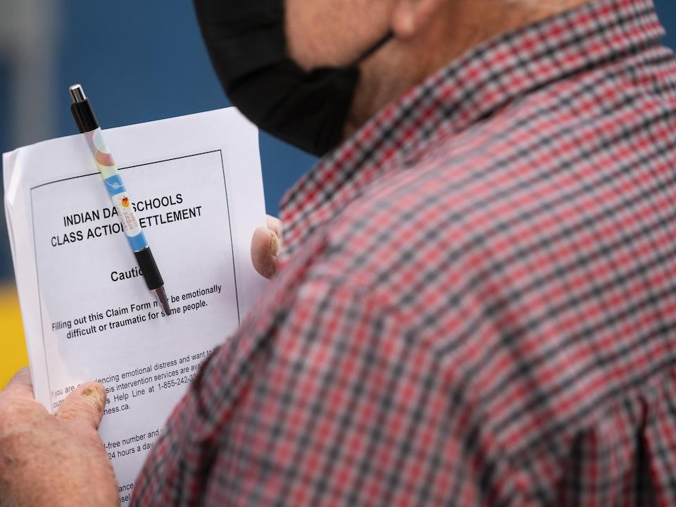 Un homme tient en main un document.