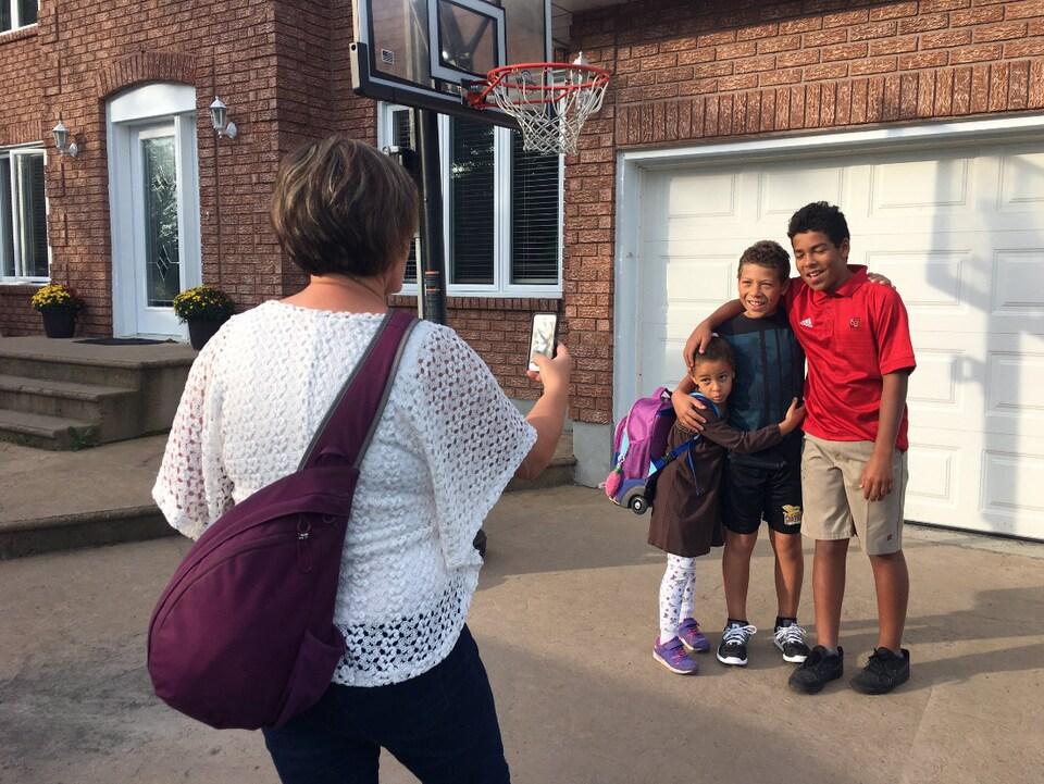 Une femme prend une photo de trois enfants devant une maison.