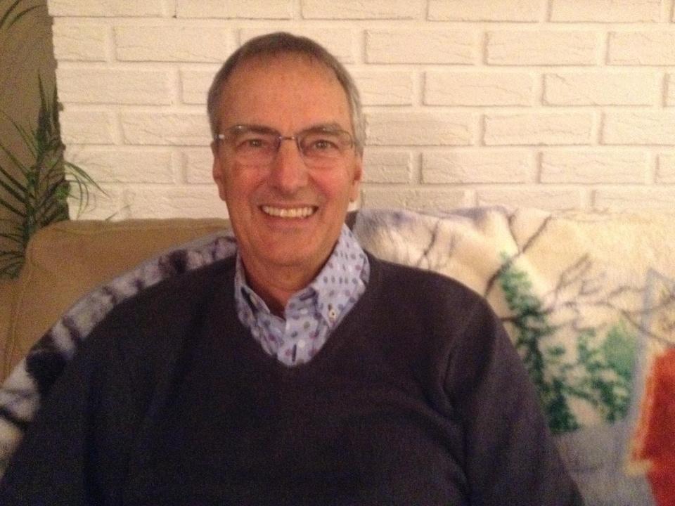 Richard Gauthier est assis dans un divan et sourit.