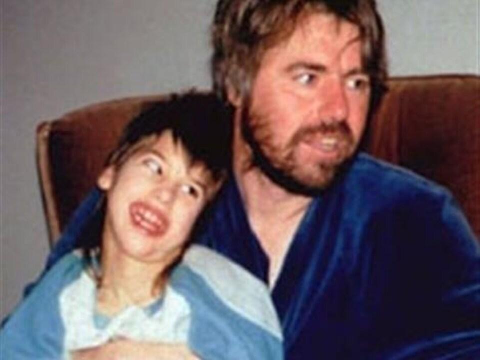 Robert Latimer tient sa fille Tracy sur ses genoux. Tous deux sourient en regardant vers leur gauche.