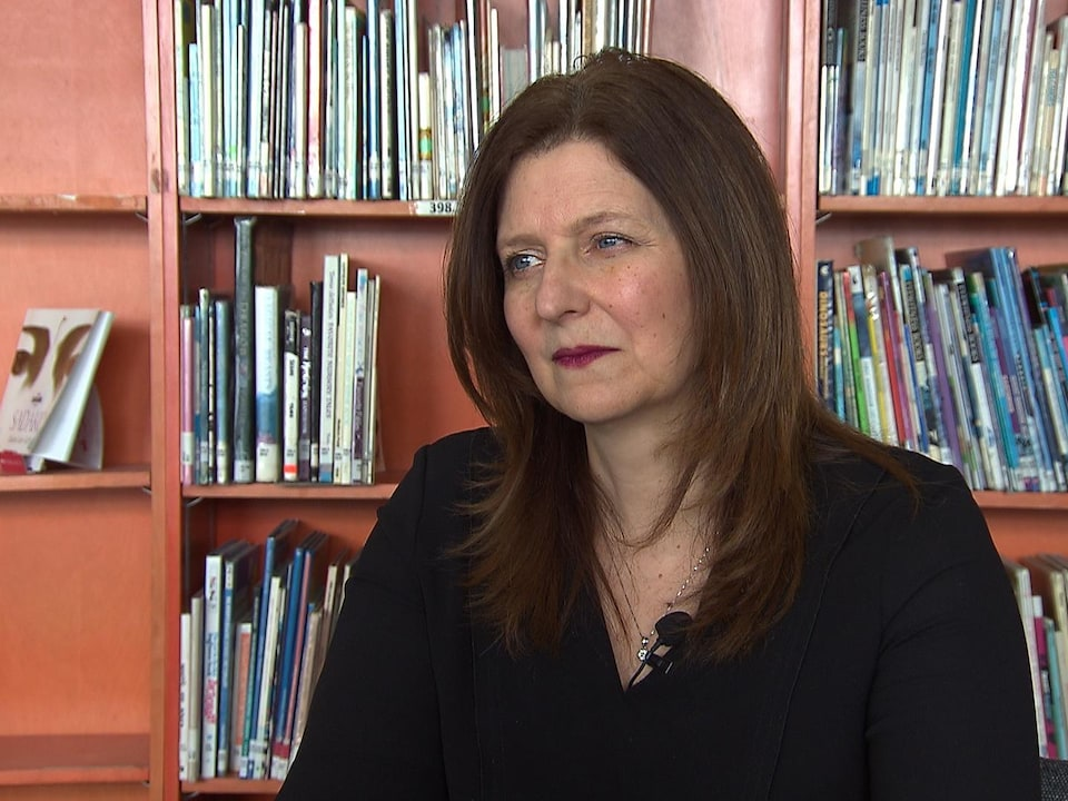 Angela Mancini devant une bibliothèque.