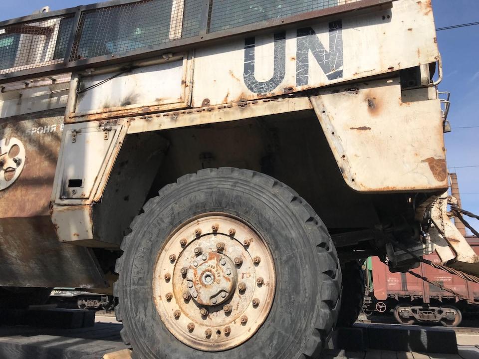 Gros plan sur la roue arrière d'un véhicule blindé attaché à l'extérieur d'un train.