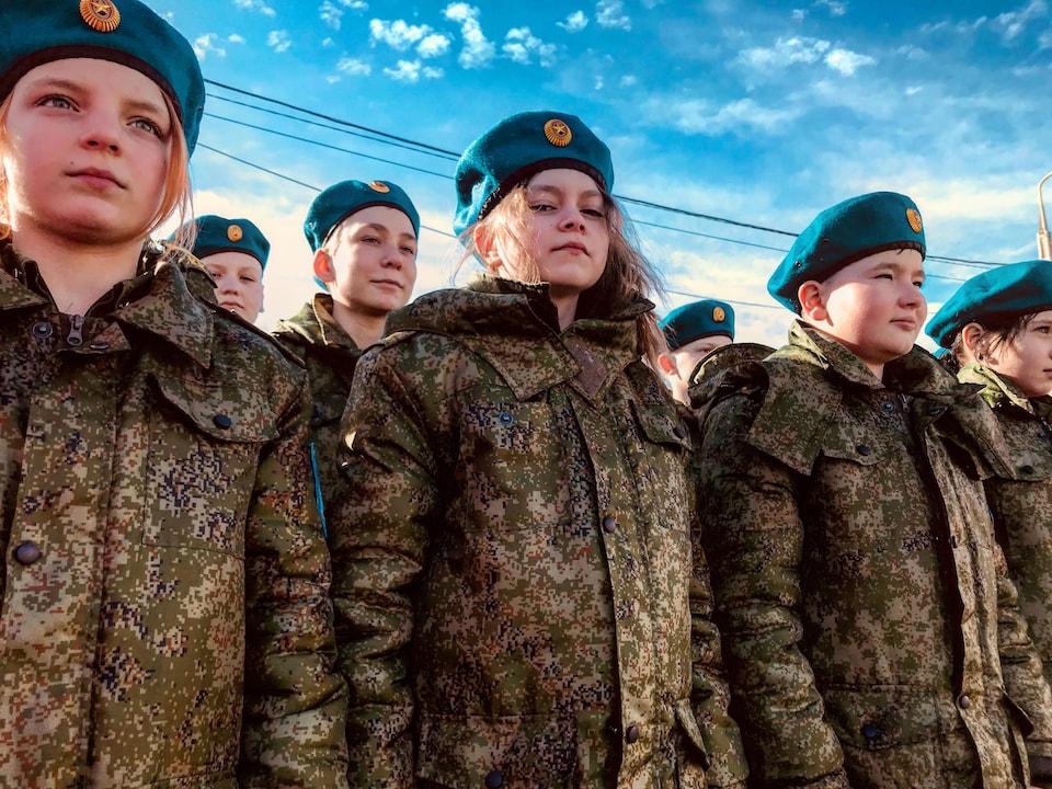 Plusieurs jeunes portant un uniforme militaire avec un béret se tiennent bien droits.