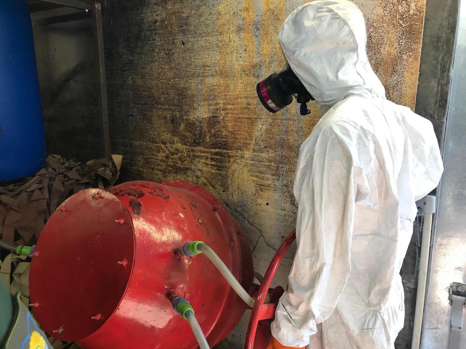 Un mannequin portant une tenue stérile blanche et un masque à gaz est debout près d'une cuve servant à préparer des mélanges chimiques.
