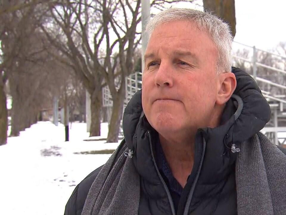 Un homme portant un manteau répond aux questions d'une journaliste dans un parc.