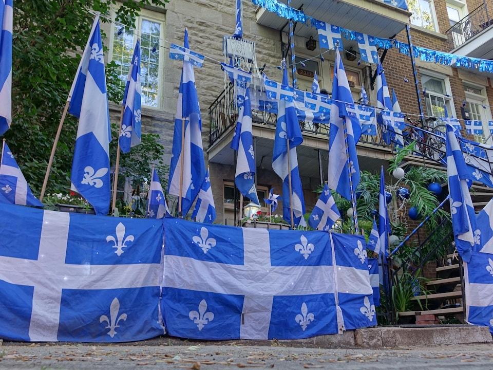 Une maison ornée de plusieurs drapeaux du Québec.