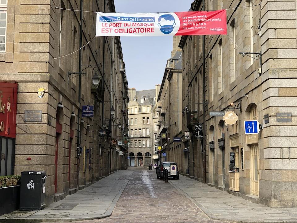 Une rue déserte avec une bannière suspendue indiquant que le port du masque est obligatoire.