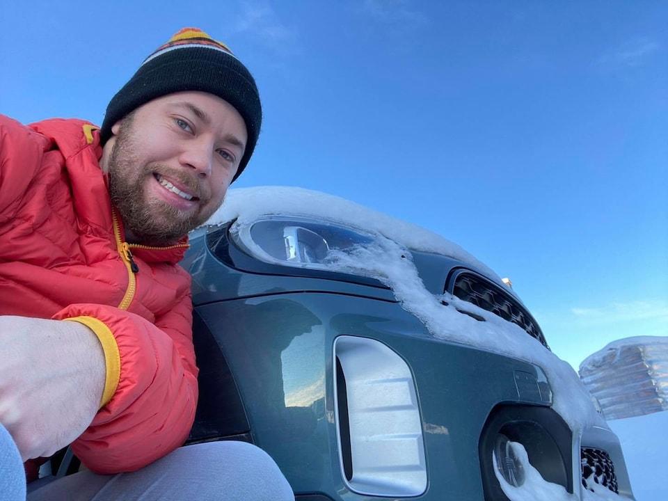 Samuel Lessard pose accroupi à côté d'une voiture.