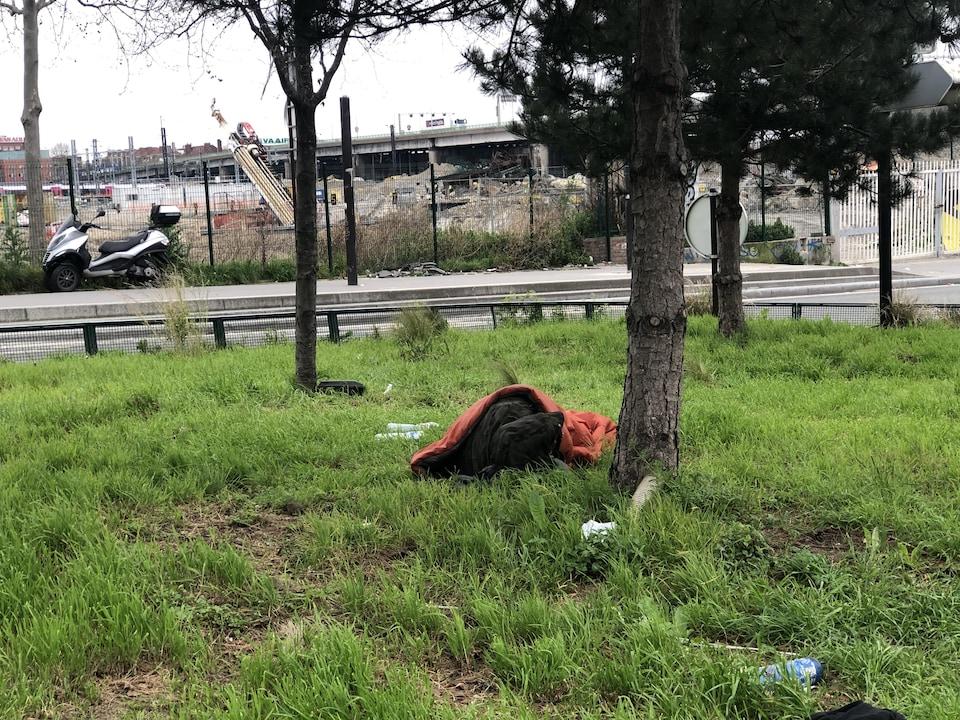 Un sans-abri allongé dans un parc à Paris, en France.