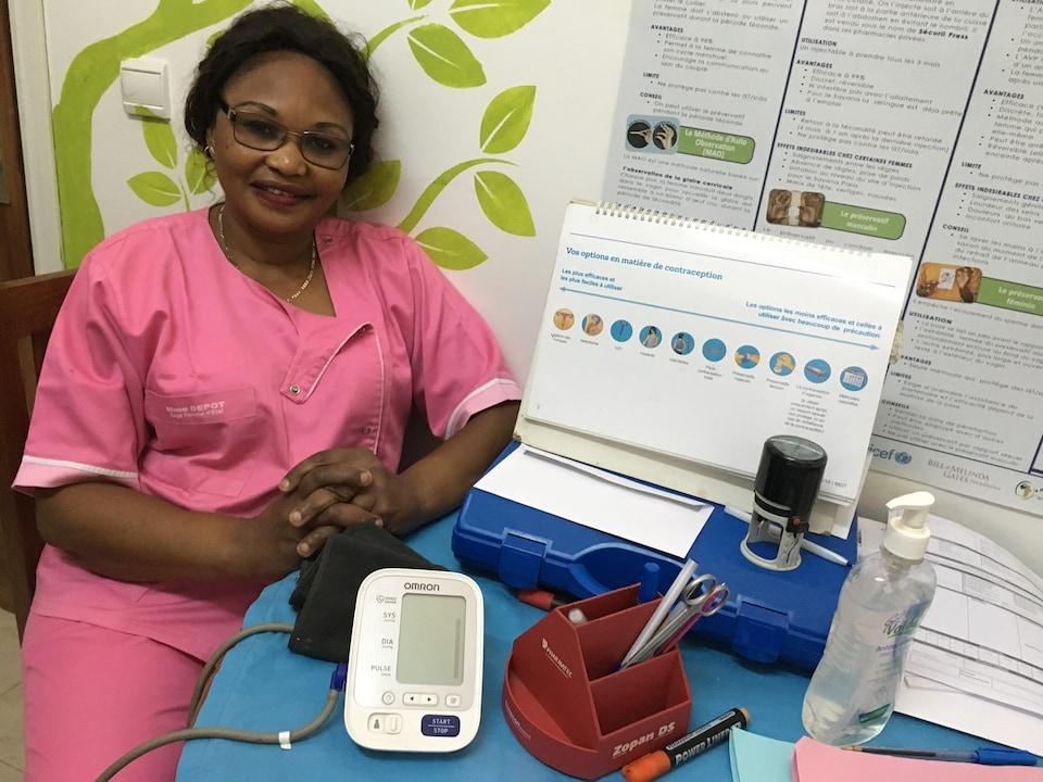 Une femme, portant un uniforme d'hôpital, est assise et nous regarde en souriant timidement. Elle est légèrement accotée sur le mur et sur la table devant elle se trouve des objets médicaux.
