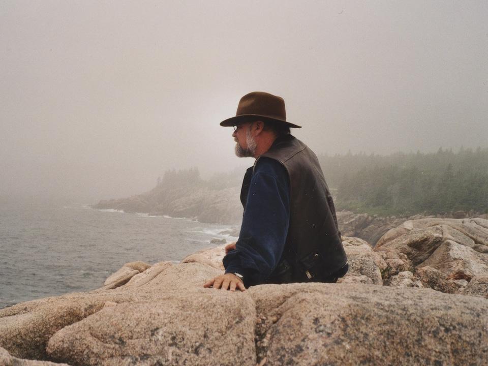 Serge Bouchard assis sur des rochers qui regarde le fleuve en Nouvelle-Écosse, près de Cabot Trail