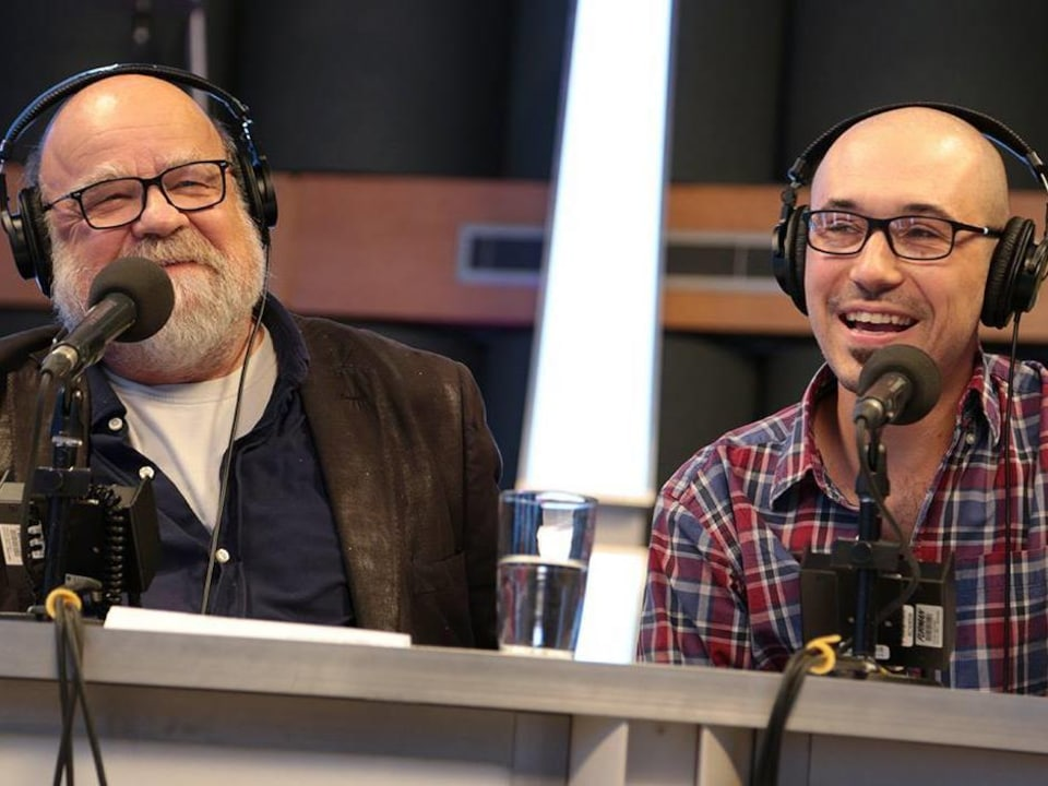 Assis l'un à côté de l'autre devant leur micro.