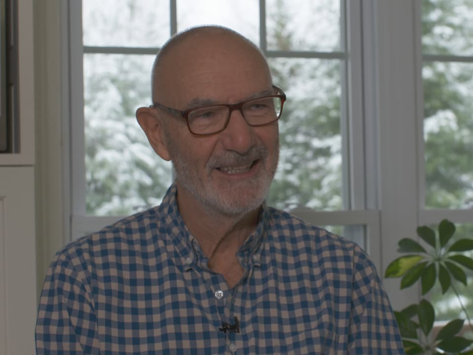 Un homme qui sourit répond aux questions d'une journaliste.