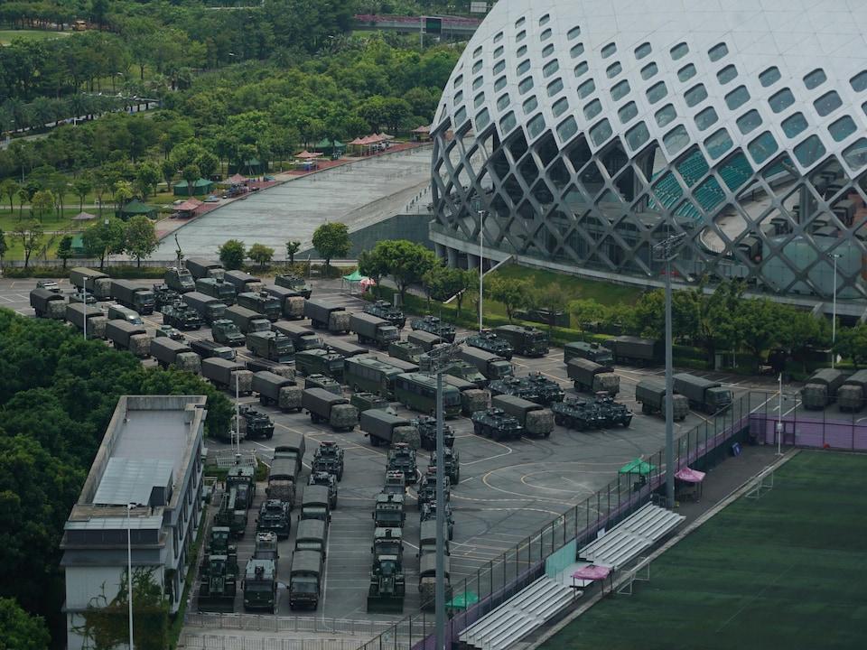 Des dizaines de véhicules sont stationnés près d'un stade.