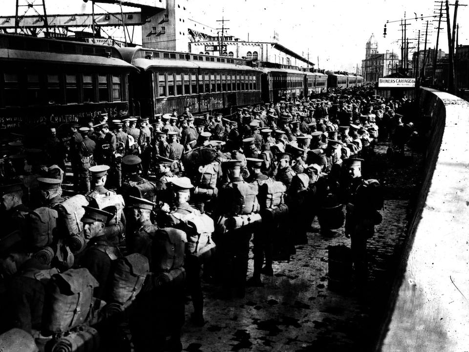 Des soldats attendent sur le quai d'une gare.