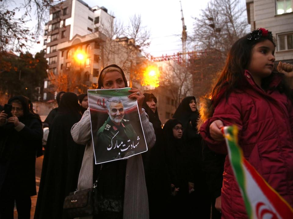 Une femme tient une photo de M. Soleimani.