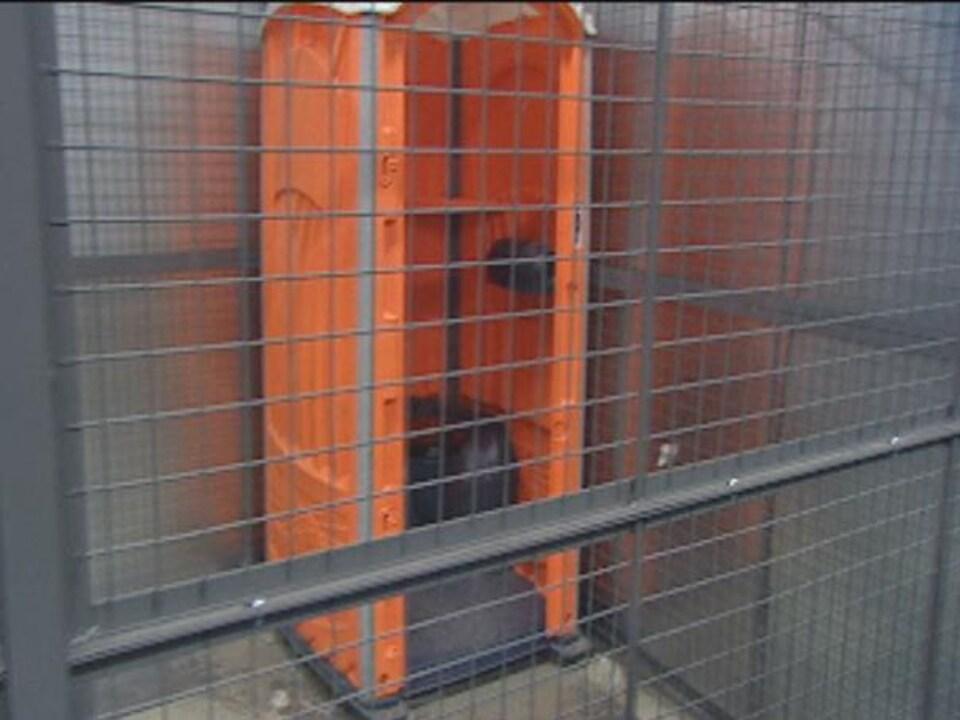 Une cage avec une toilette sans porte.