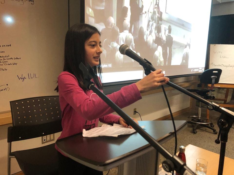 Une jeune fille parle devant un micro.