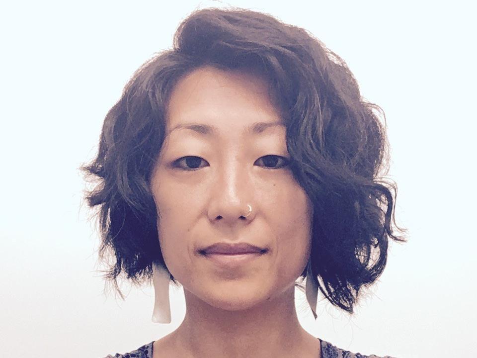 Portrait d'une femme au nez percé qui porte des boucles d'oreilles.