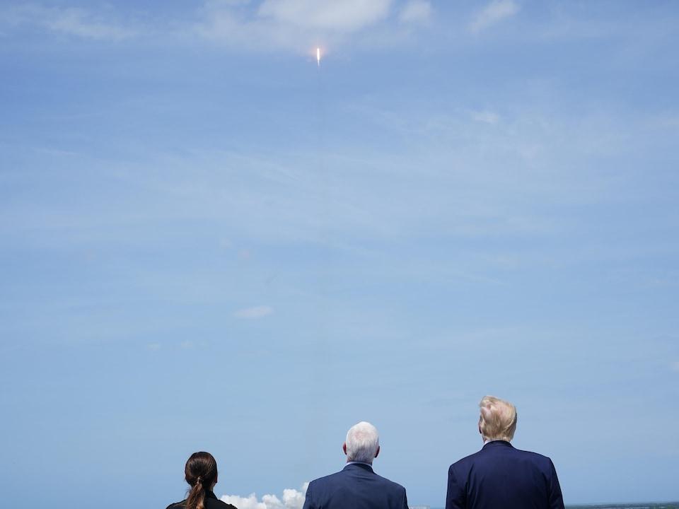 Mike Pence et Donald Trump, de dos, regardant vers un ciel bleu dégagé une fusée s'élevant vers l'espace.