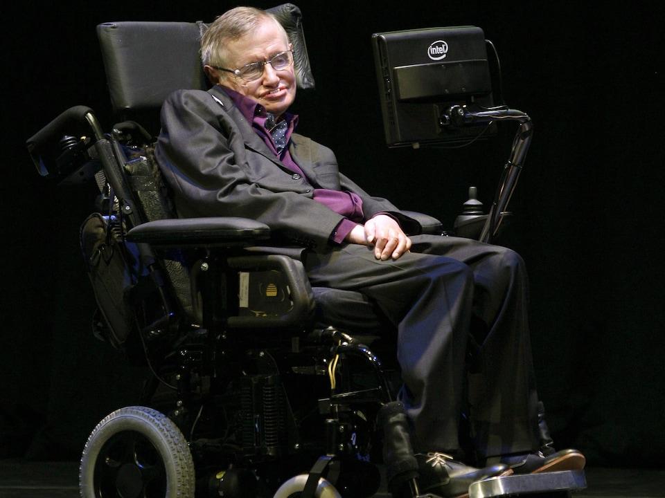 Le scientifique dans son fauteuil roulant regarde un écran.