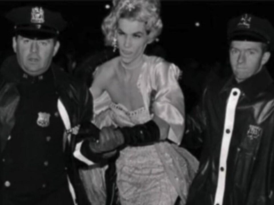 Une personne, coiffée d'une perruque et vêtue d'une robe, est menottée et escortée par deux policiers.