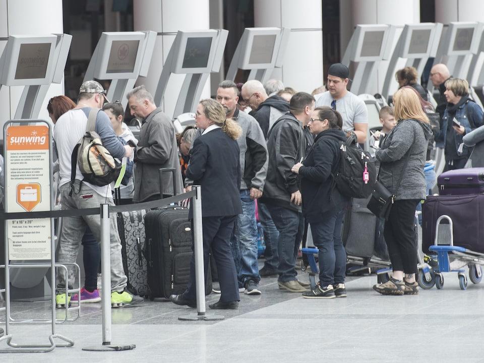 Des voyageurs en file devant les bornes de Sunwing à l'aéroport de Montréal.