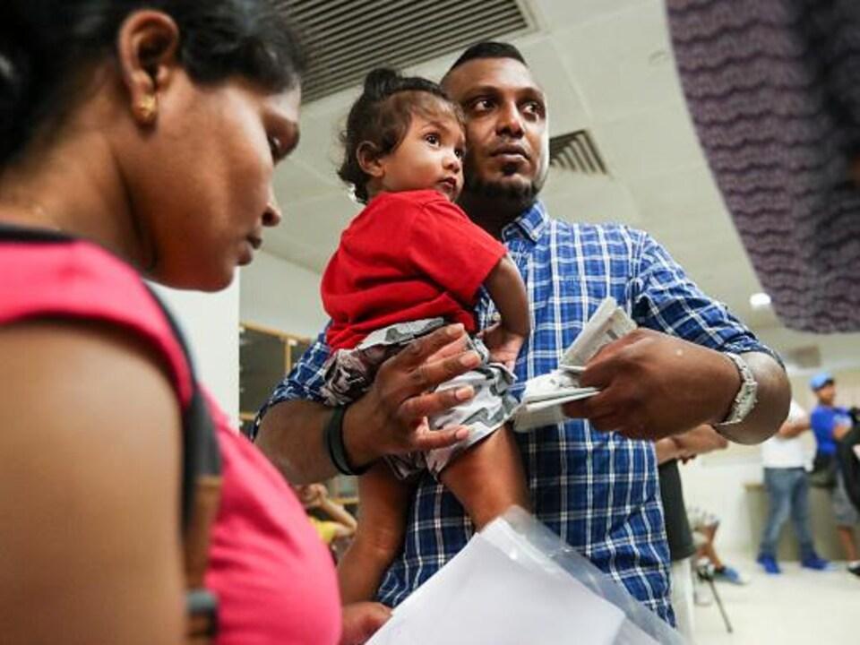 Supun tient son fils Dinath dans les bras, aux côtés de sa femme Nadeeka, juste après avoir appris le rejet de leur demande d'asile à Hong Kong, en 2017.