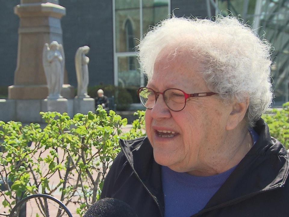 Gros plan sur le visage de Suzanne Tremblay qui répond aux questions d'une journaliste.