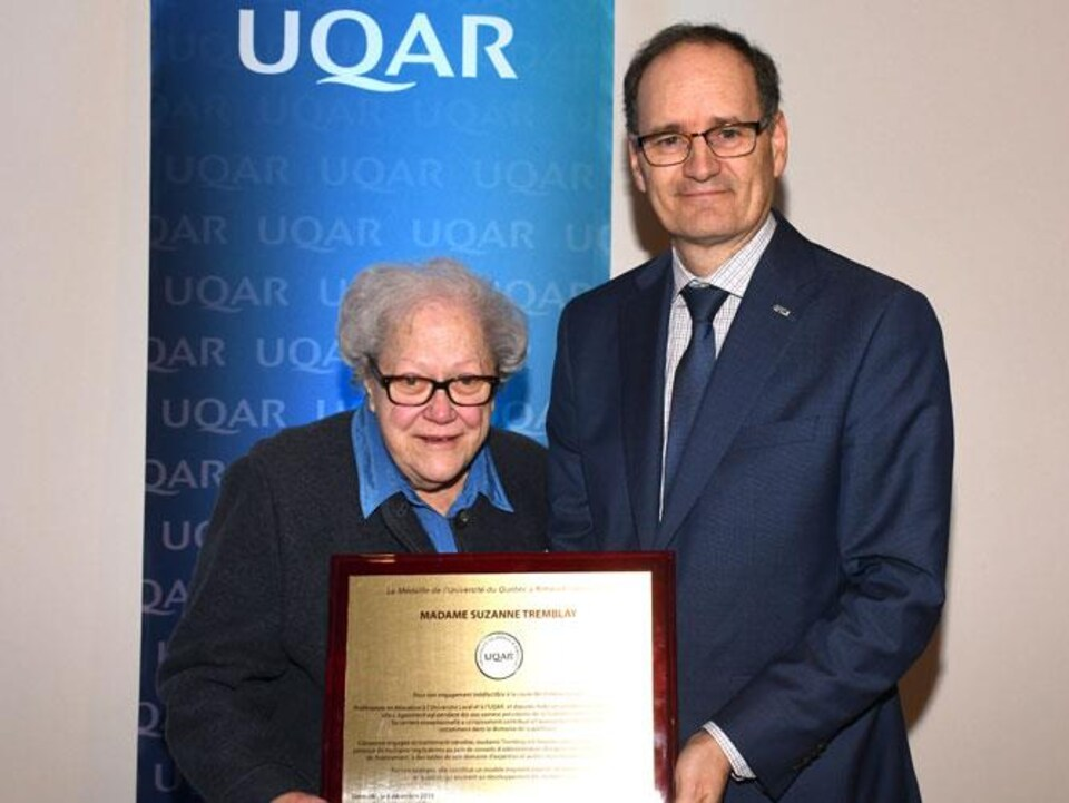 Suzanne Tremblay pose avec une plaque honorifique. Jean-Pierre Ouellet se tient à ses côtés.