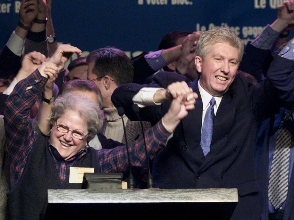 Suzanne Tremblay et Gilles Duceppe, parmi d'autres bloquistes, se tiennent par la main et sourient.