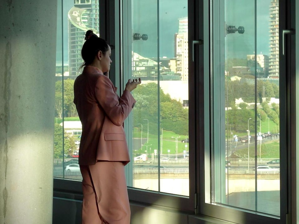 Une femme est devant la baie vitrée d'un immeuble.