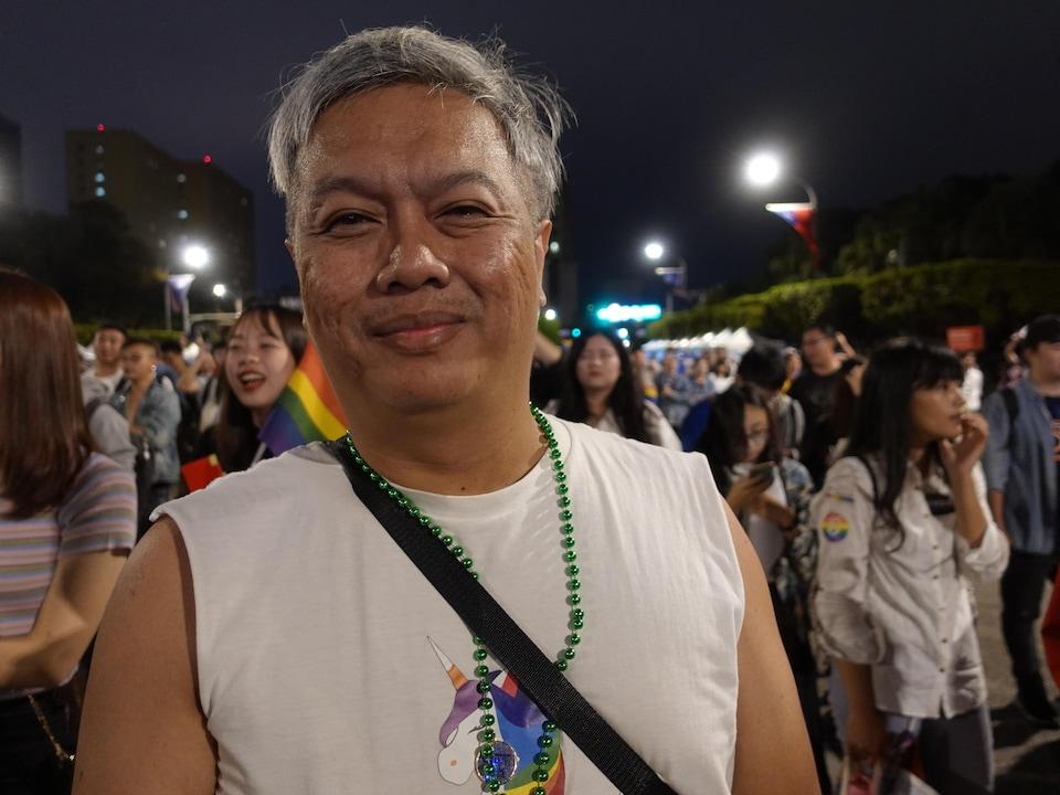 Simat, un participant de la Marche des Fiertés de Taïwan, est venu d'Indonésie. Il se trouve dans la foule qui assiste à un spectacle à Taipei; la nuit est tombée sur  la capitale. 26 octobre 2019