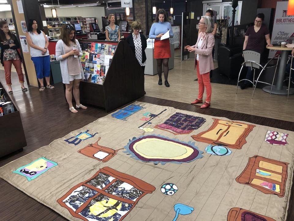 Une femme présente un tapis de lecture dans une bibliothèque.