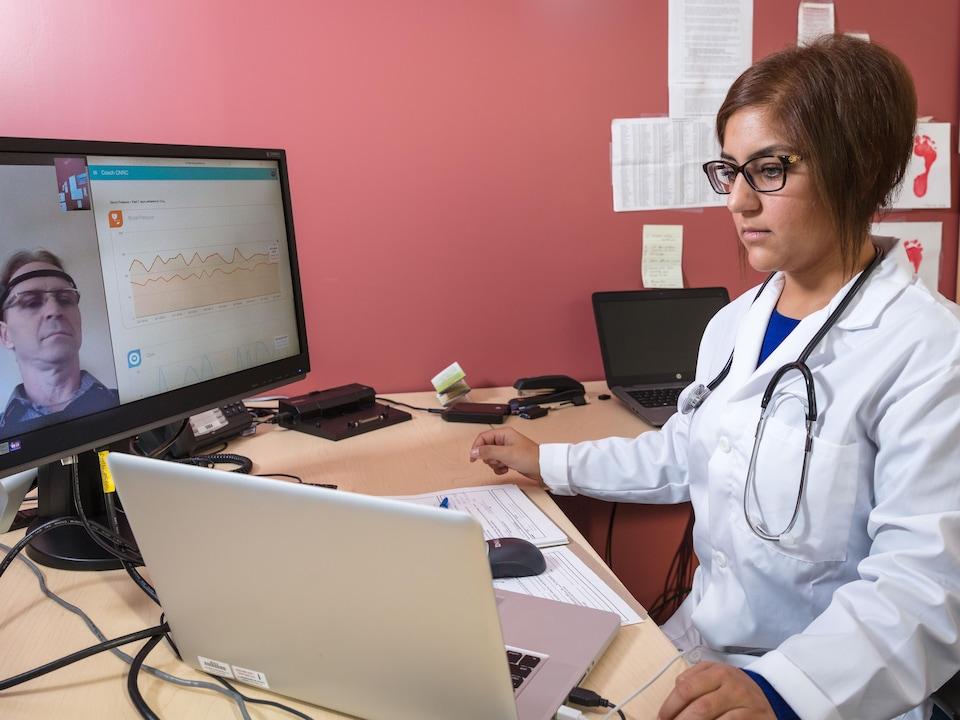 On voit une femme en sarrau assise devant un ordinateur. Elle a un stéthoscope autour du cou. Sur l'écran, on voit le visage d'un participant à une étude.