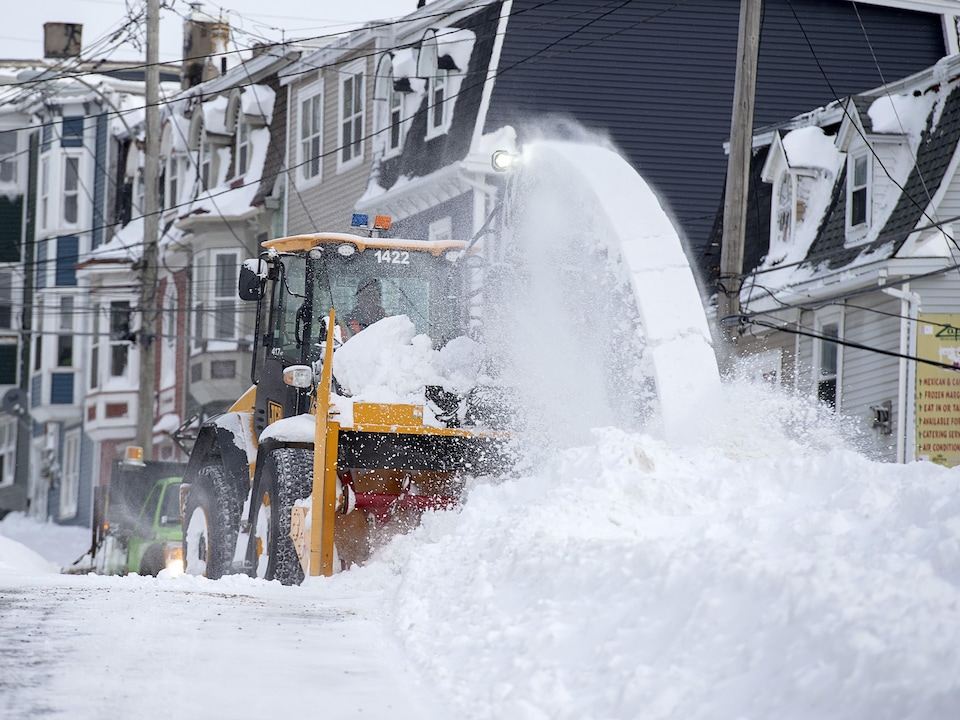 Les employés de la ville déblaient la neige avec leur machinerie.
