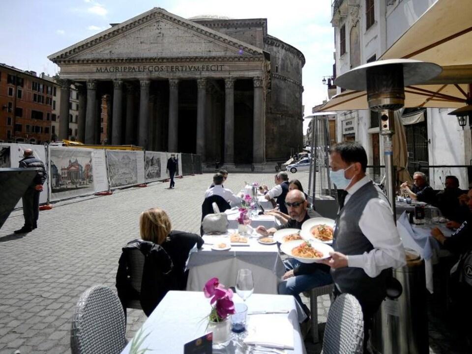 Un serveur amène des plats de pâtes à des clients assis sur la terrasse extérieure, tout près du Panthéon.
